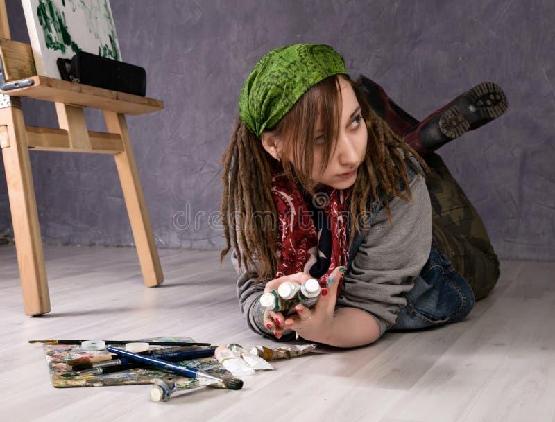 El artista de sexo femenino creativo miente cuidadosamente en el piso foto de archivo