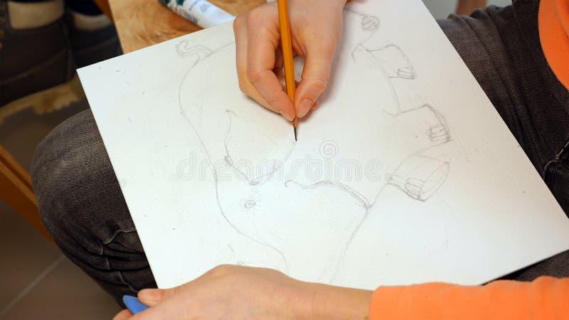 El artista de sexo femenino dibuja un bosquejo del lápiz en estudio del arte fotografía de archivo