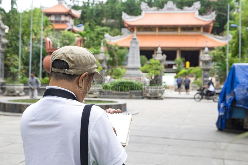 El artista de sexo masculino dibuja un bosquejo de la pagoda larga del hijo, Nha Trang fotografía de archivo