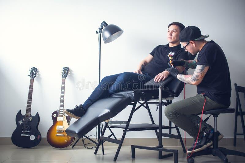 El artista del tatuaje hace el tatuaje a mano imágenes de archivo libres de regalías