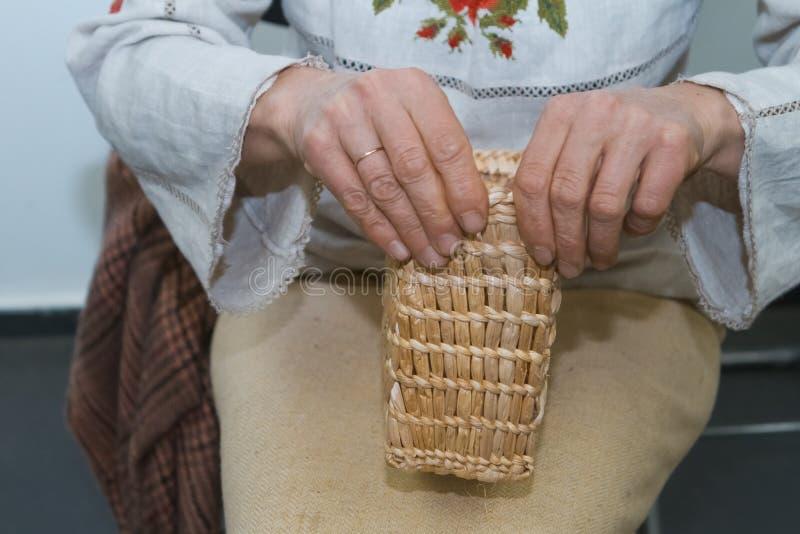 El artista experto de la mujer trenza un bolso de la paja, arte tradicional del arte, material ecológico, tela fotos de archivo libres de regalías