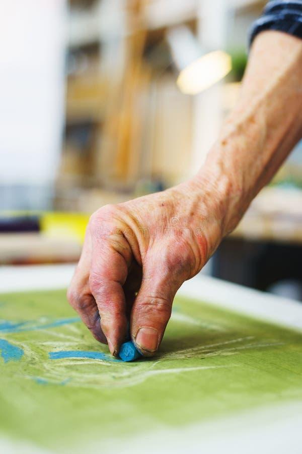 El artista hace el primer srihi en lona en curso de dibujo con los creyones en colores pastel imagenes de archivo