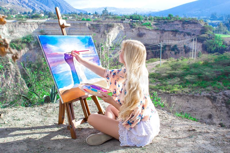 El artista hermoso de la mujer joven pinta un paisaje en naturaleza Dibujo en el caballete con las pinturas coloridas en el aire  fotos de archivo