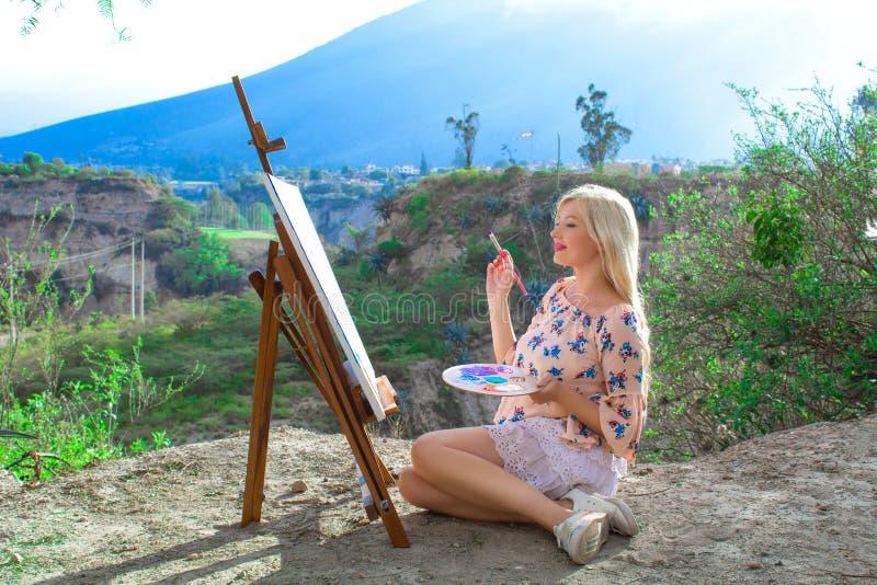 El artista hermoso de la mujer joven pinta un paisaje en naturaleza Dibujo en el caballete con las pinturas coloridas en el aire  fotos de archivo libres de regalías