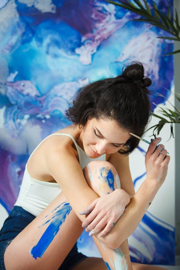 El artista joven crea las nuevas ilustraciones que se sientan en piso Mujer seria imagen de archivo libre de regalías