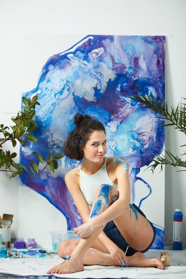 El artista joven crea las nuevas ilustraciones que se sientan en piso Mujer seria imagenes de archivo