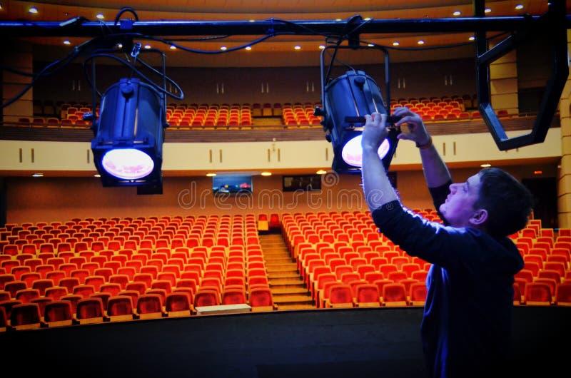 El artista ligero monta los accesorios de iluminación en el teatro imagen de archivo