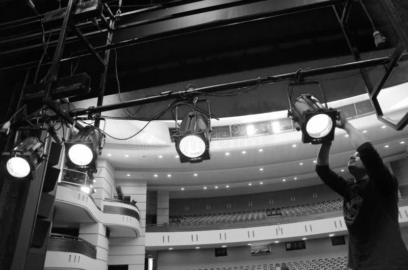 El artista ligero monta los accesorios de iluminación en el teatro foto de archivo