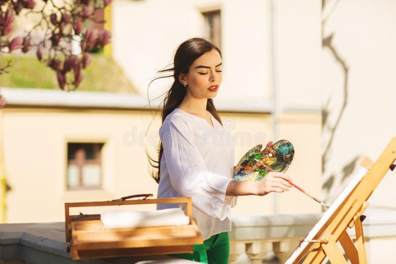 El artista moreno sonriente joven de la mujer pinta una imagen en la calle, cerca de un ?rbol hermoso de la magnolia fotos de archivo