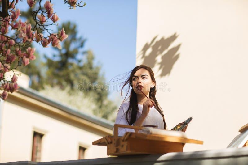 El artista moreno sonriente joven de la mujer pinta una imagen en la calle, cerca de un ?rbol hermoso de la magnolia imagen de archivo libre de regalías