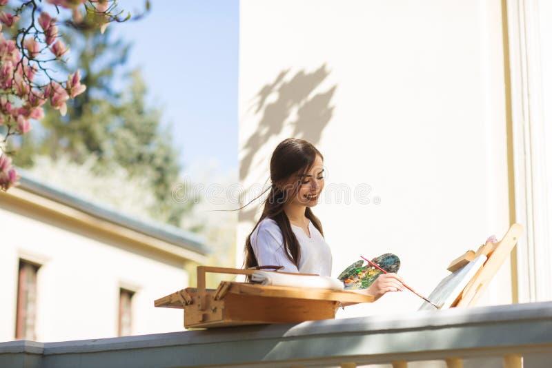 El artista moreno sonriente joven de la mujer pinta una imagen en la calle, cerca de un ?rbol hermoso de la magnolia fotos de archivo libres de regalías