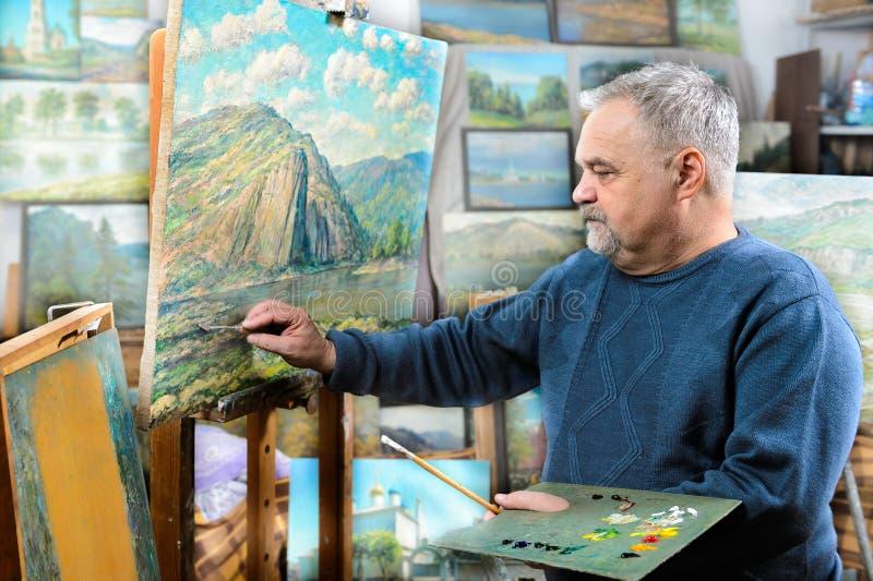 El artista pinta la pintura al óleo con un cepillo y una paleta fotografía de archivo