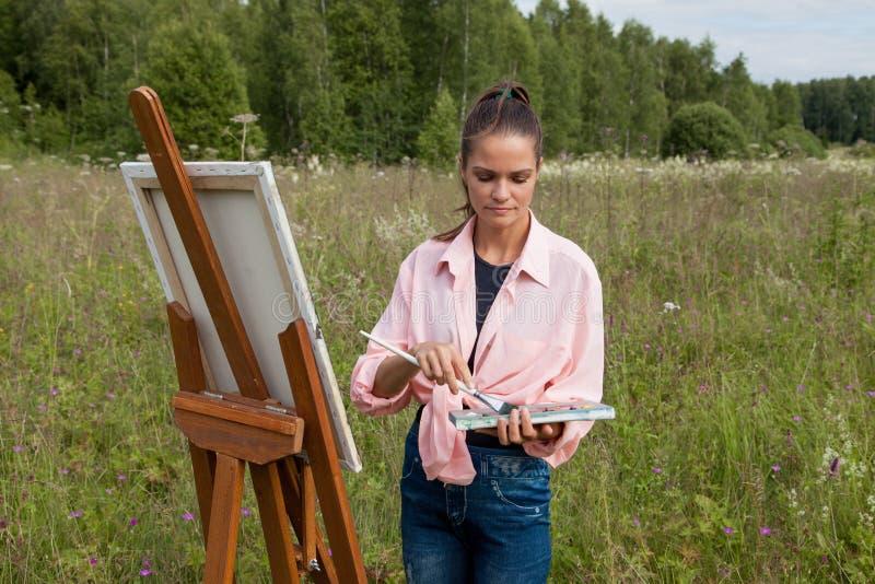 El artista pinta una imagen en el campo foto de archivo