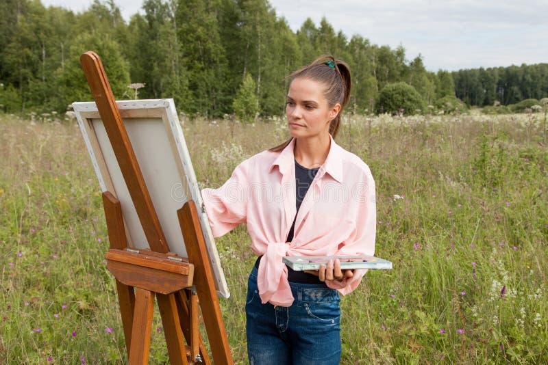 El artista pinta una imagen en el campo imagen de archivo libre de regalías