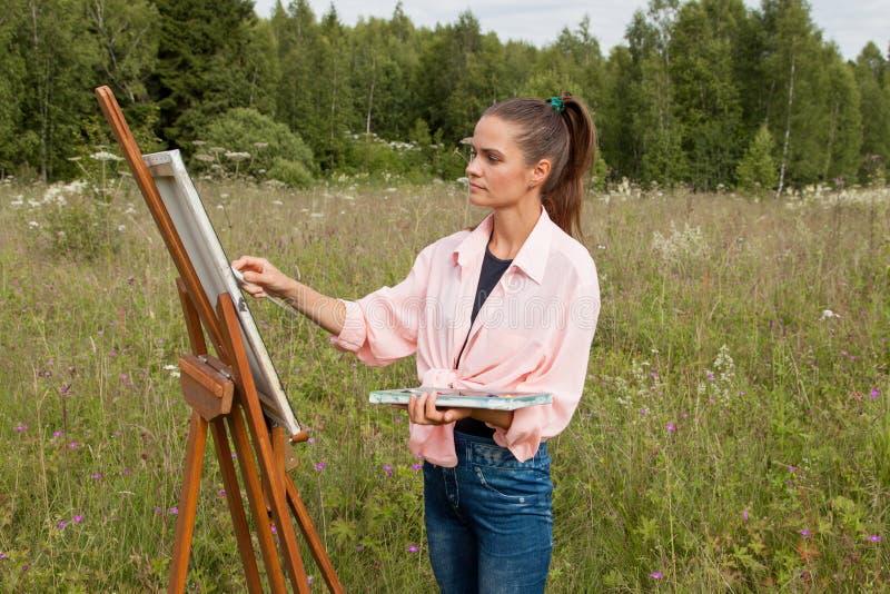 El artista pinta una imagen en el campo imágenes de archivo libres de regalías