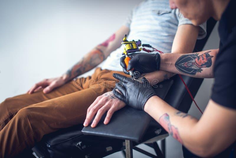 El artista principal del tatuaje en guantes hace el tatuaje imágenes de archivo libres de regalías