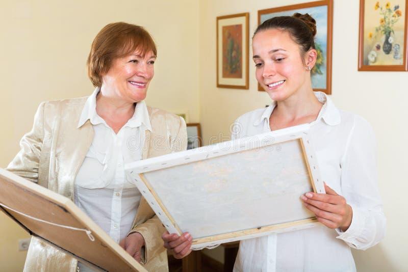 El artista sonriente de las mujeres vende las ilustraciones imagen de archivo libre de regalías