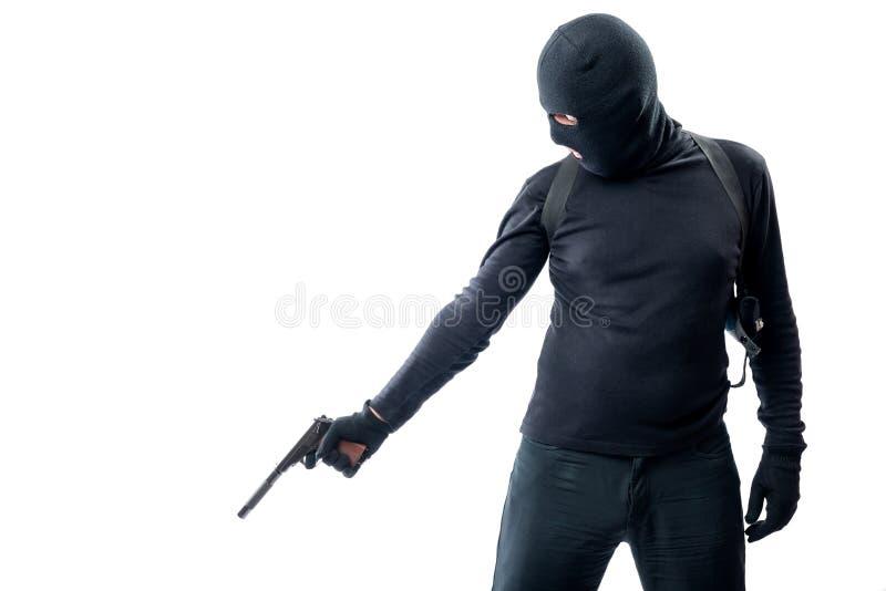 El asesino enciende una pistola con un silenciador en una persona de mentira fotos de archivo