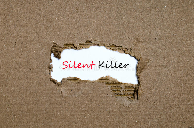 El asesino silencioso de la palabra que aparece detrás del papel rasgado imagen de archivo libre de regalías