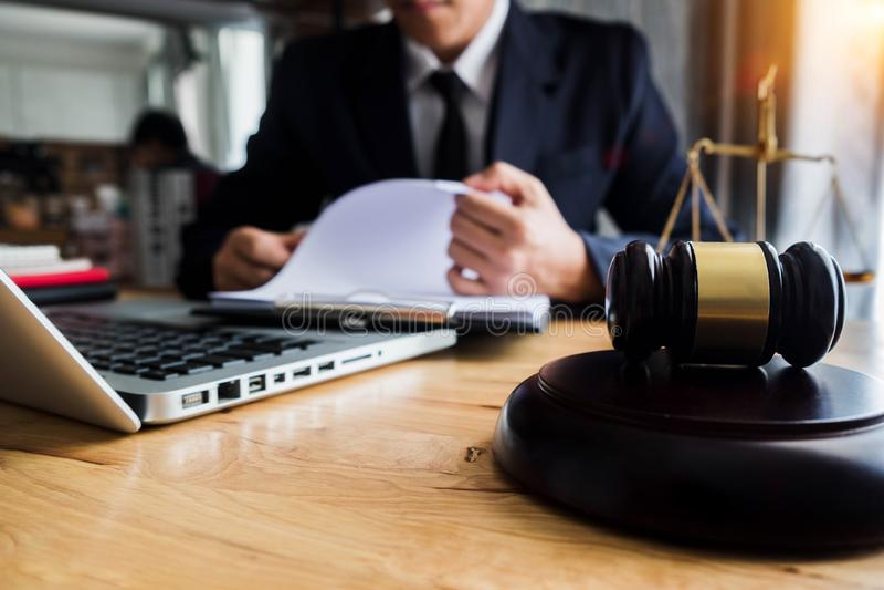 El asesor legal presenta al cliente un contrato firmado con el mazo y la ley legal foto de archivo