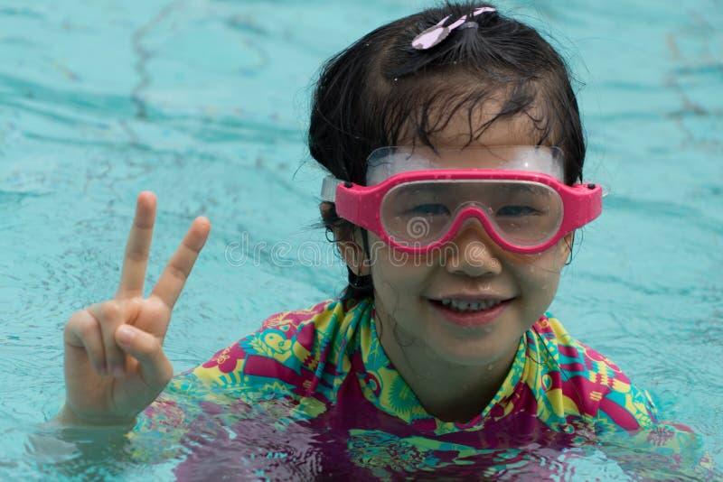 El asiático de la forma de vida de la juventud de las gafas de la sonrisa de la nadada de la muchacha goza de traje de baño foto de archivo