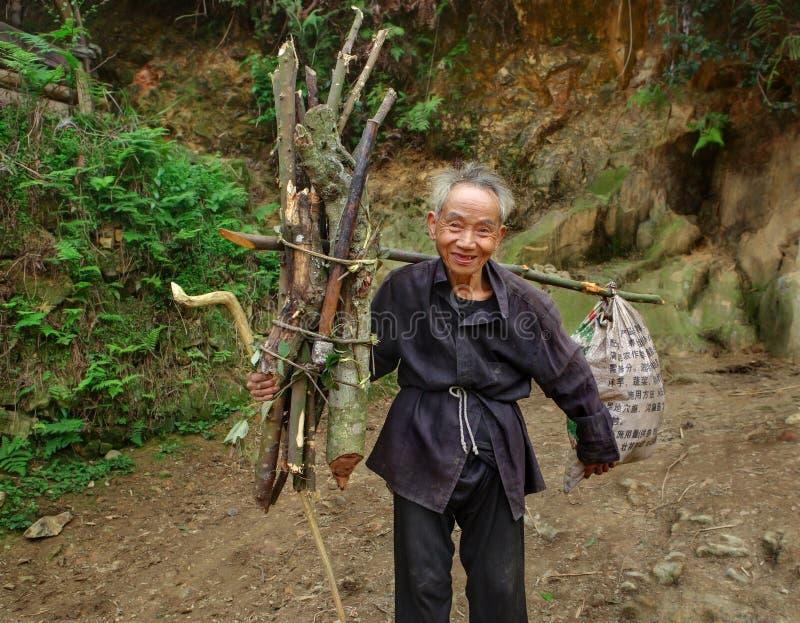El asiático del viejo hombre, con los haces de leña del manojo, va en rastro de montaña. foto de archivo libre de regalías