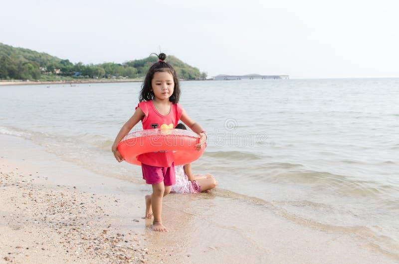 El asiático embroma a la muchacha tailandesa que juega en las vacaciones de verano de la playa foto de archivo