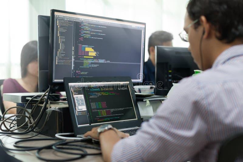 El asiático externaliza el desarrollador que considera la pantalla que se sienta el funcionamiento del escritorio fotografía de archivo