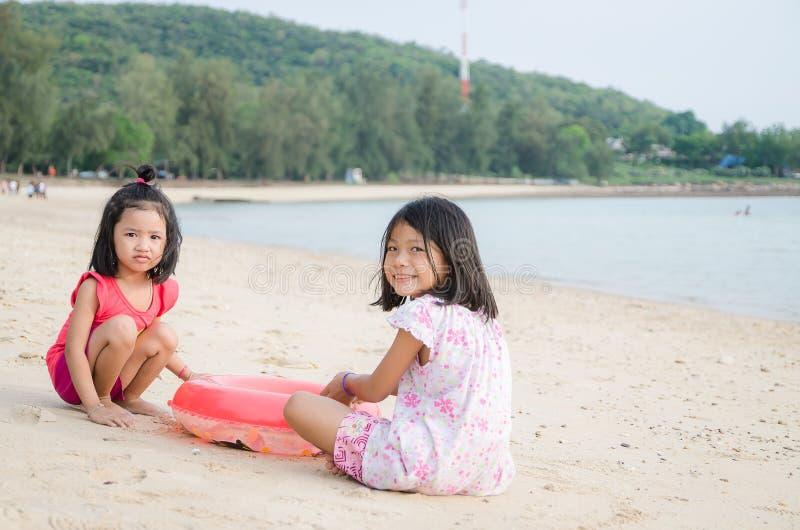 El asiático feliz de la sonrisa embroma al niño tailandés de la muchacha que juega la arena en el beac imagen de archivo