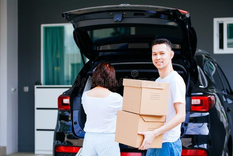 El asiático feliz maduro casó las cajas de cartón de la pareja que llevaban del tronco de coche en el nuevo hogar fotos de archivo