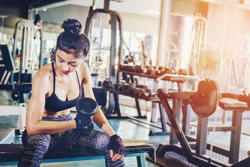 El asiático se divierte a la mujer que hace ejercicios con los pesos de la pesa de gimnasia en gimnasio foto de archivo