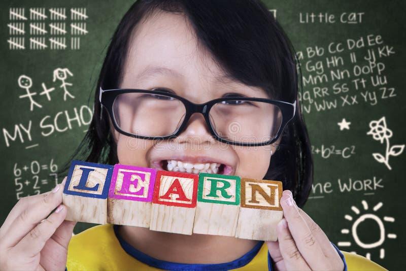 El asimiento del graduado de la muchacha del primer aprende el juguete de madera en clase fotos de archivo libres de regalías