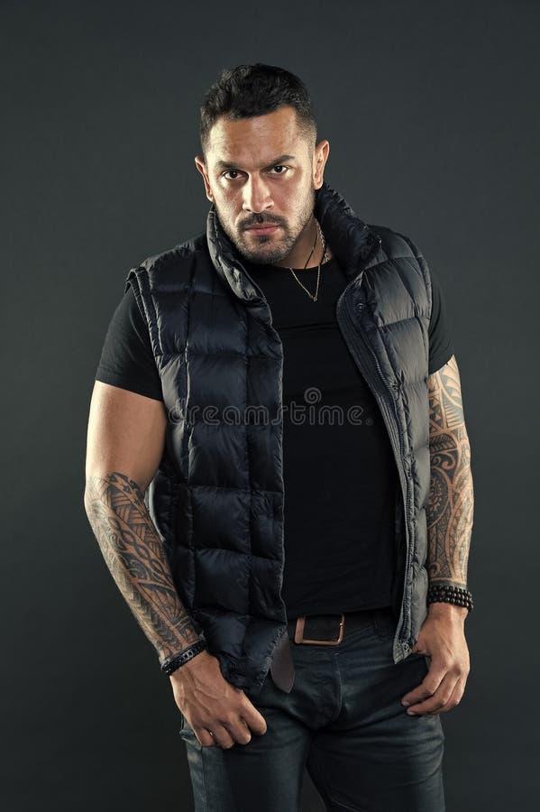 El aspecto hisp?nico sin afeitar brutal del hombre tatu? los brazos Hombre barbudo que presenta con los tatuajes Machista estrict imagenes de archivo