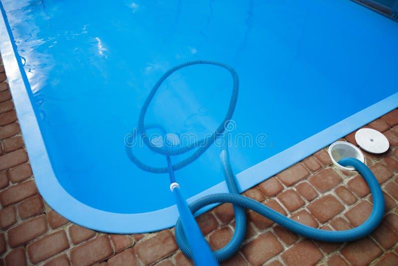 El aspirador para la piscina, limpia y cuida para la parte inferior de la piscina recoja, absorba la basura y la suciedad imagenes de archivo