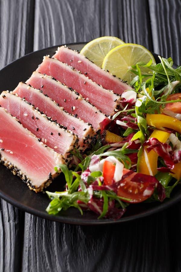 El atún chamuscado del ahi cubrió las semillas de sésamo con la ensalada en el cl de la placa negra imagenes de archivo