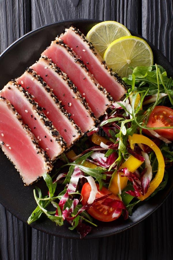 El atún chamuscado del ahi cubrió las semillas de sésamo con la ensalada en el cl de la placa negra imagen de archivo