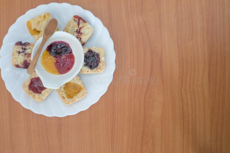 El atasco hecho en casa del arándano y el atasco anaranjado y la mermelada de fresa llenaron las galletas gastrónomas de la mig foto de archivo