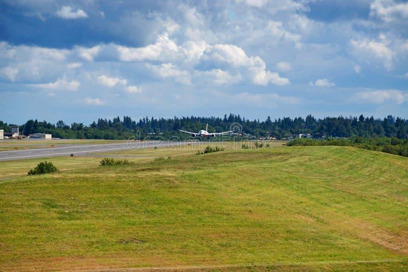 El aterrizaje de aeroplano en pista con el cielo azul llenó de las nubes imágenes de archivo libres de regalías