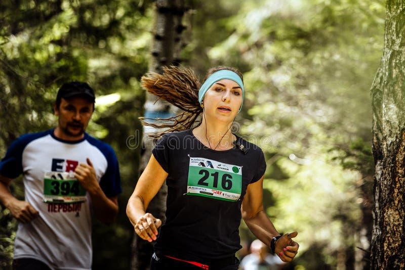 El atleta activo joven de la mujer corre en el bosque, pelo flojo fotografía de archivo libre de regalías