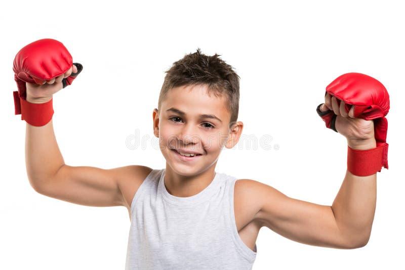 El atleta alegre del muchacho aumentó sus manos para arriba en guantes rojos del karate, con un gesto de la victoria, en un fondo fotografía de archivo libre de regalías