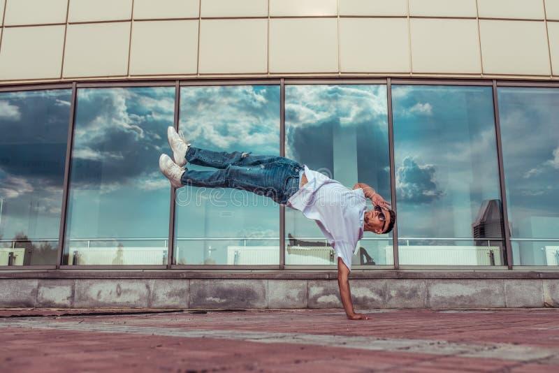 El atleta bailarín con camiseta blanca, jeans, salta su brazo, ciudad de verano, lentes de sol, vidrieras de fondo, cadera activa fotografía de archivo libre de regalías