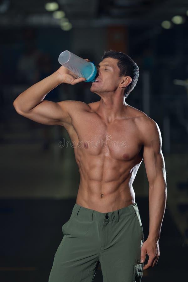 El atleta con el cuerpo muscular bebe el agua foto de archivo