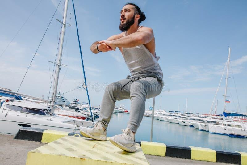 El atleta de la aptitud que hace salto se pone en cuclillas en la plyo-caja de expediente en el embarcadero del mar del verano fotografía de archivo libre de regalías