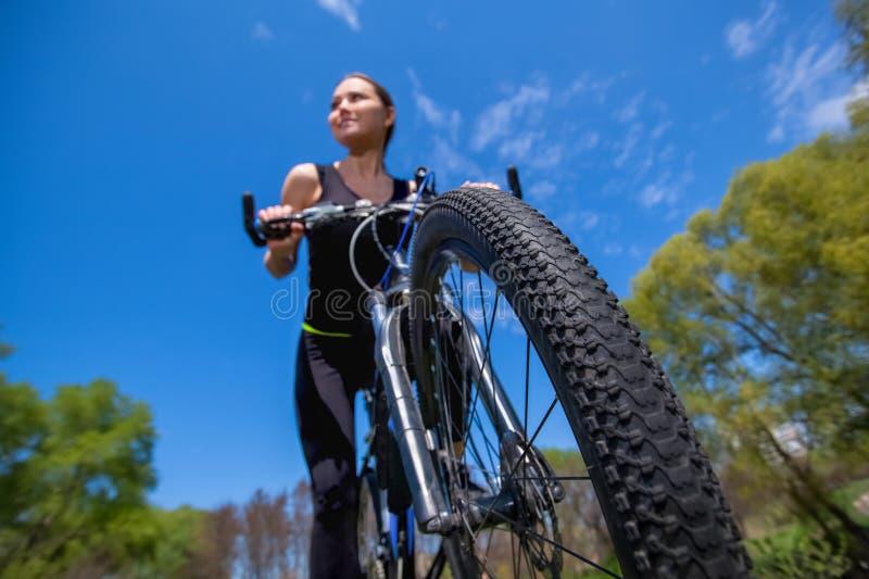 El atleta de la muchacha en chándal negro monta una bici por la mañana en el parque fotos de archivo