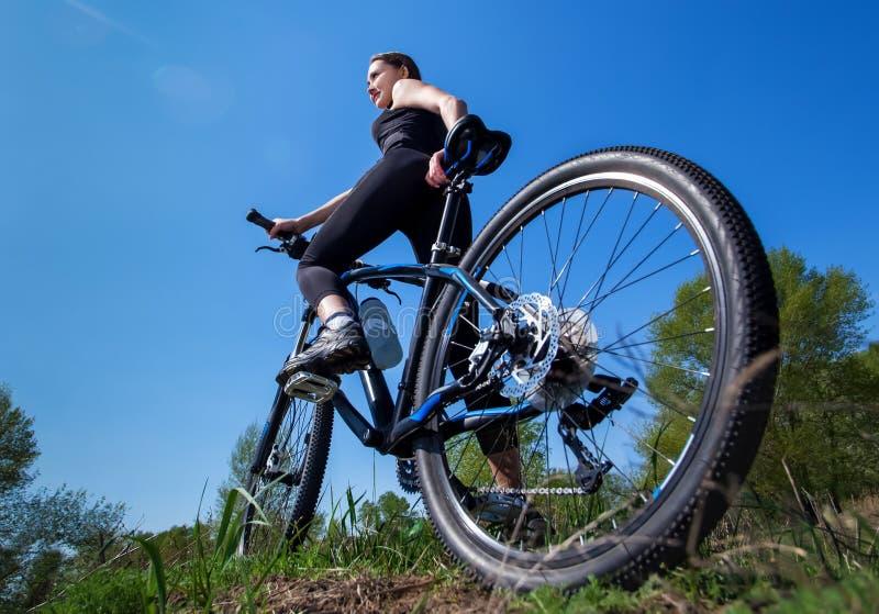 El atleta de la muchacha en chándal negro monta una bici por la mañana en el parque foto de archivo libre de regalías