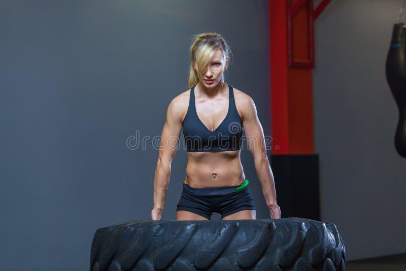 El atleta de sexo femenino apto que se resuelve con un neumático enorme, dando vuelta y lleva adentro el gimnasio Mujer de Crossf foto de archivo libre de regalías