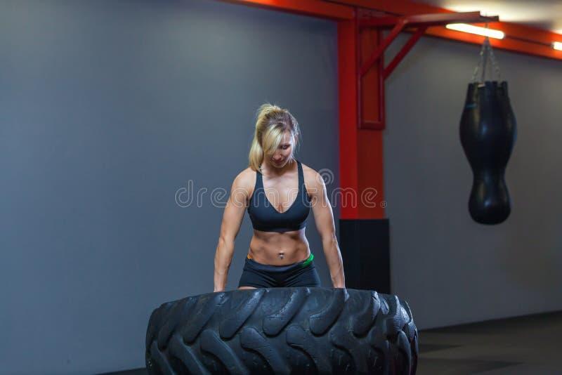 El atleta de sexo femenino apto que se resuelve con un neumático enorme, dando vuelta y lleva adentro el gimnasio Mujer de Crossf imagen de archivo