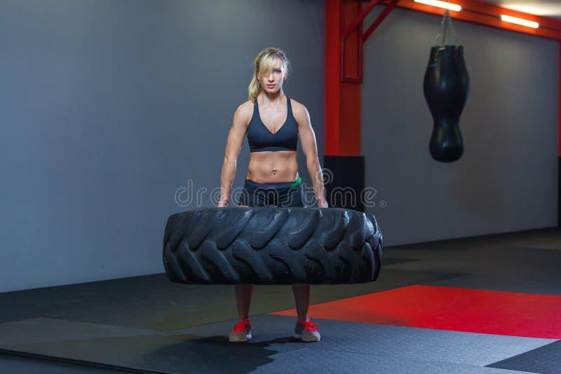 El atleta de sexo femenino apto que se resuelve con un neumático enorme, dando vuelta y lleva adentro el gimnasio Mujer de Crossf imágenes de archivo libres de regalías