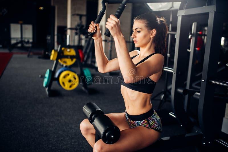 El atleta de sexo femenino entrena en la máquina del ejercicio en gimnasio imágenes de archivo libres de regalías