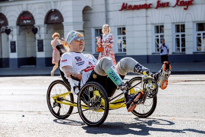 El atleta de sexo masculino con una incapacidad en una silla de ruedas monta a través de las calles de la ciudad fotografía de archivo libre de regalías